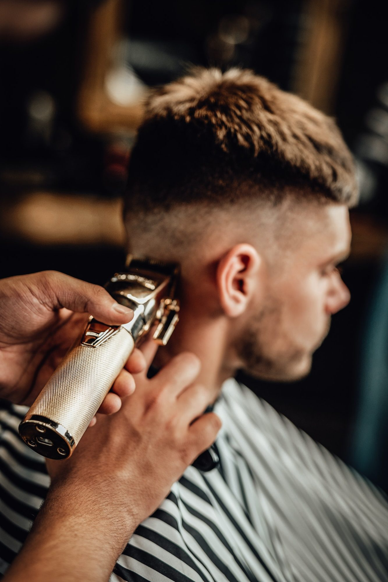 Barber cutting guy's hars with silver clipper in saloon
