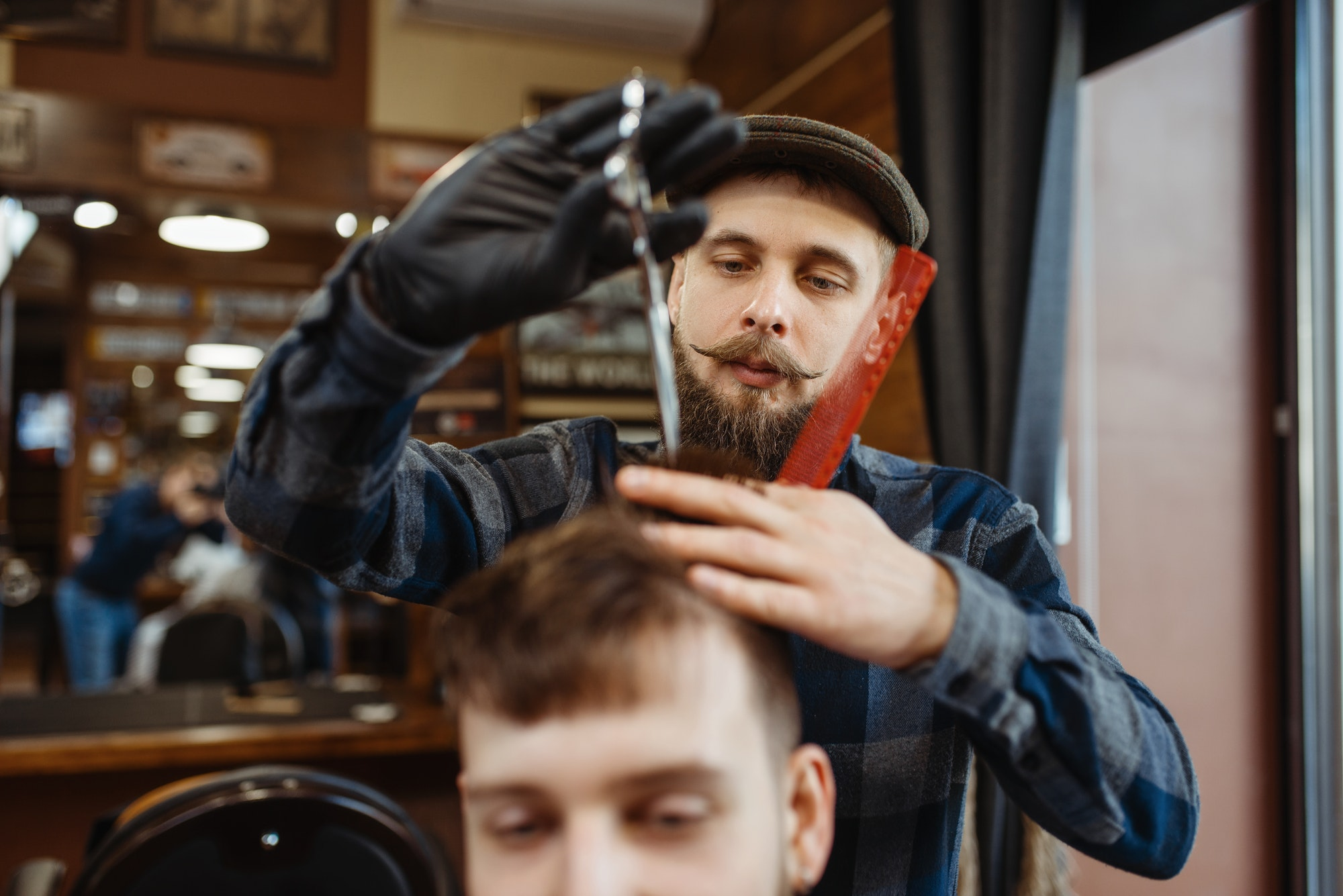 Barber makes stylish haircut to client, barbershop