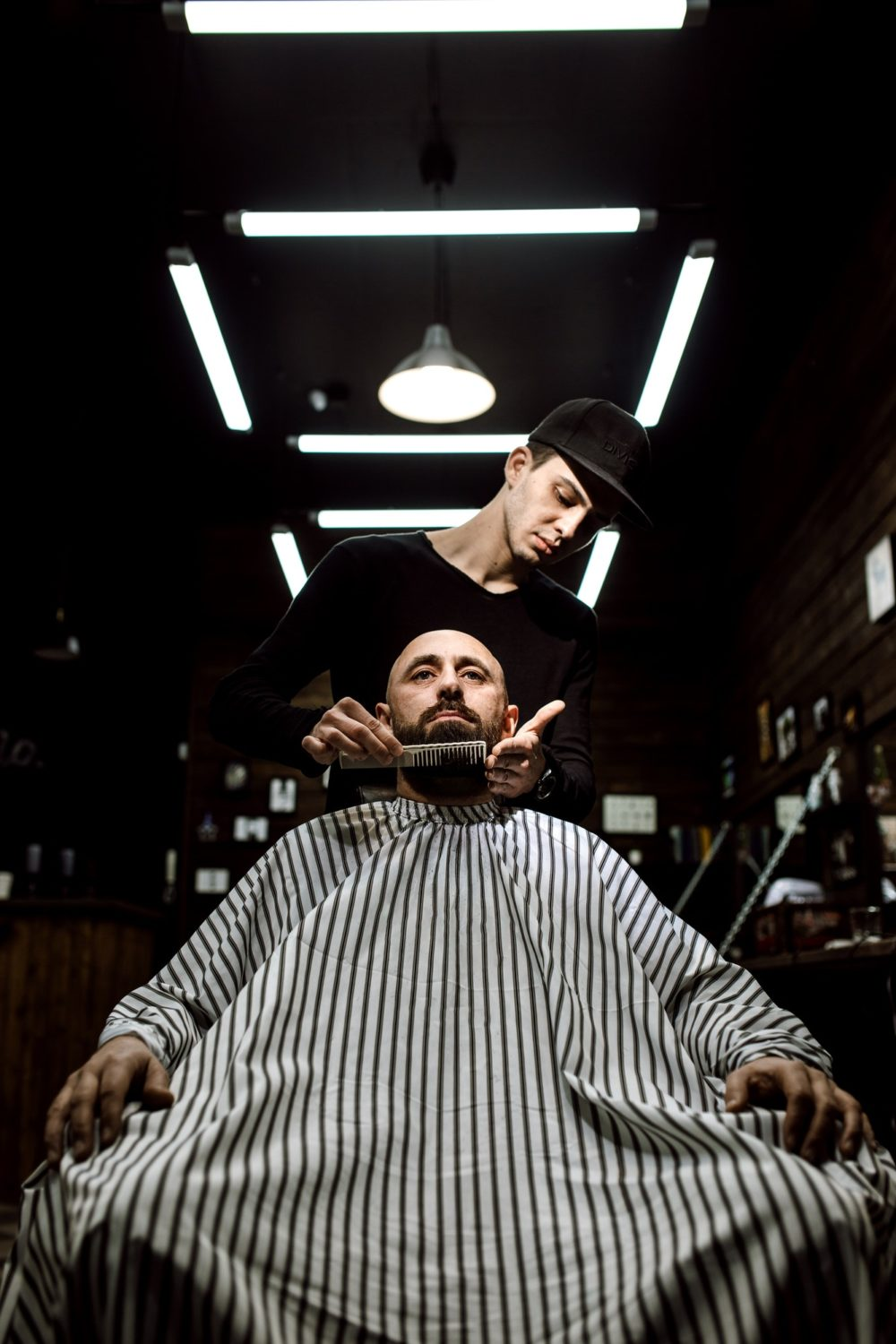 The stylish barbershop. The fashion barber tidies up beard of brutal man sitting in the armchair
