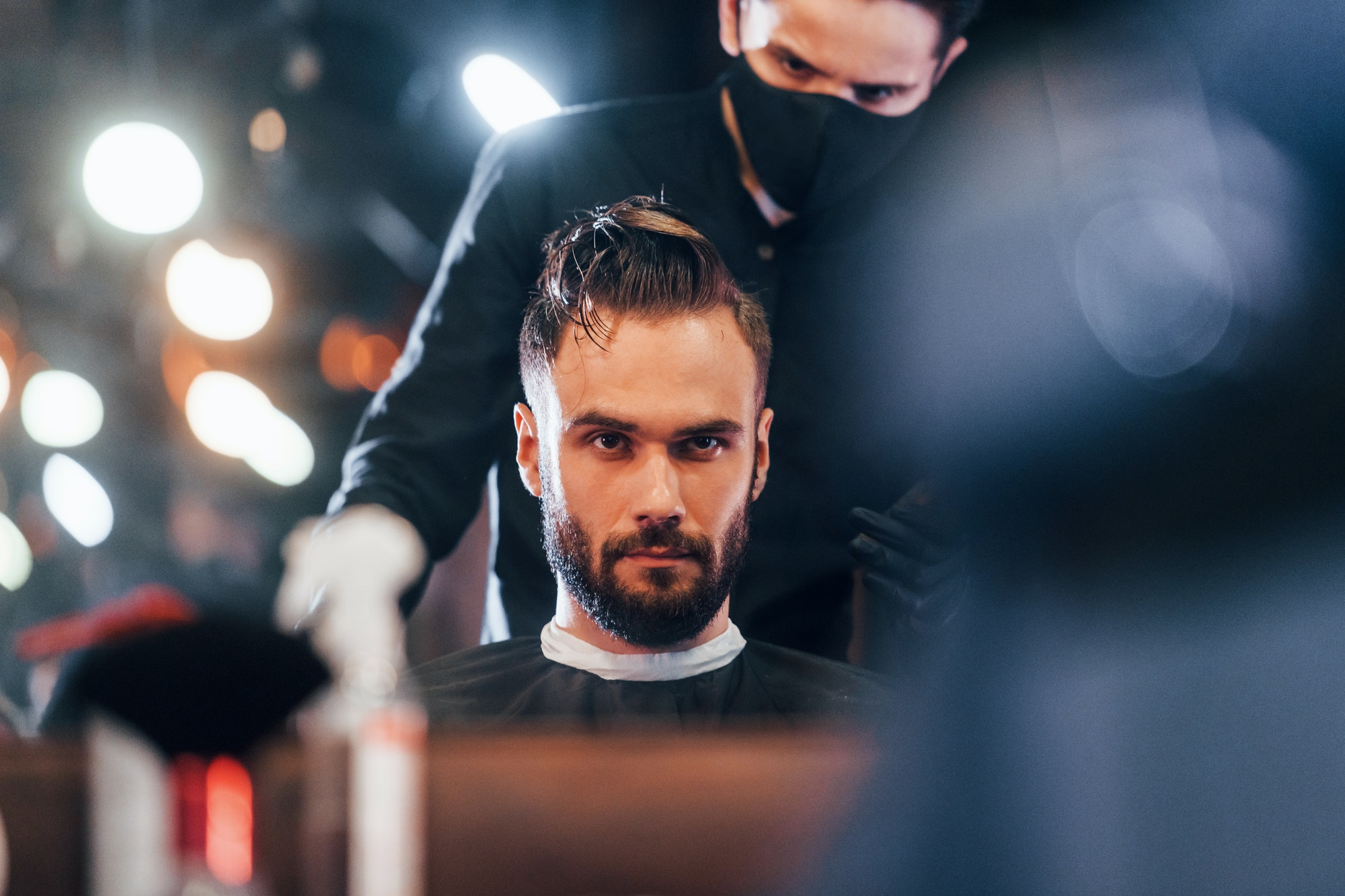 Young stylish man sitting in barbershop