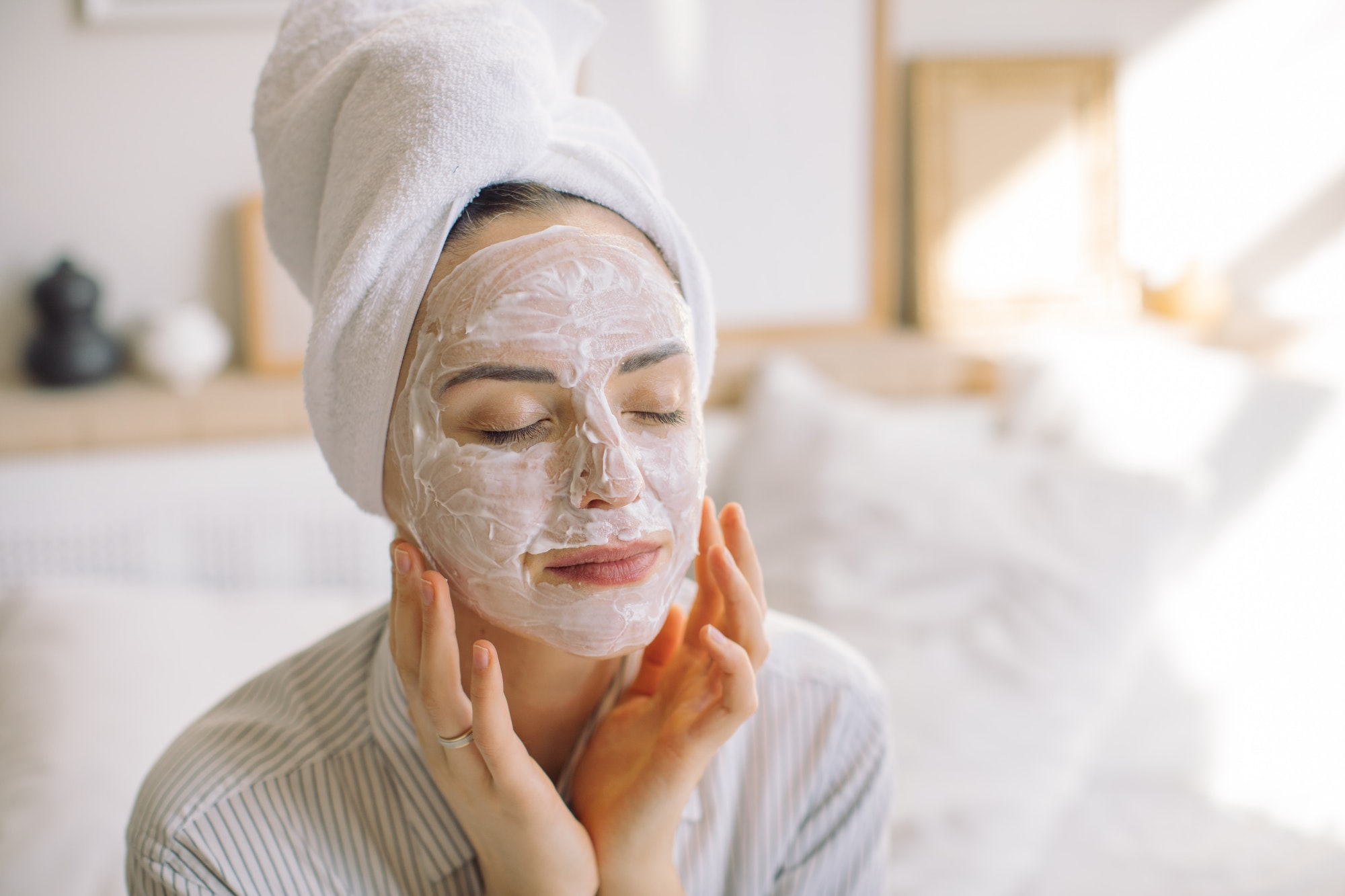 Young woman making face mask in the morning at home.