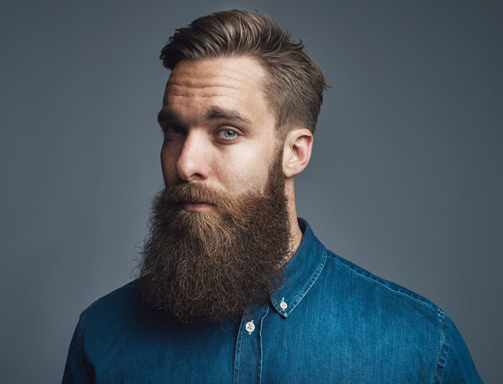 Bearded young hipster standing alone against a gray background