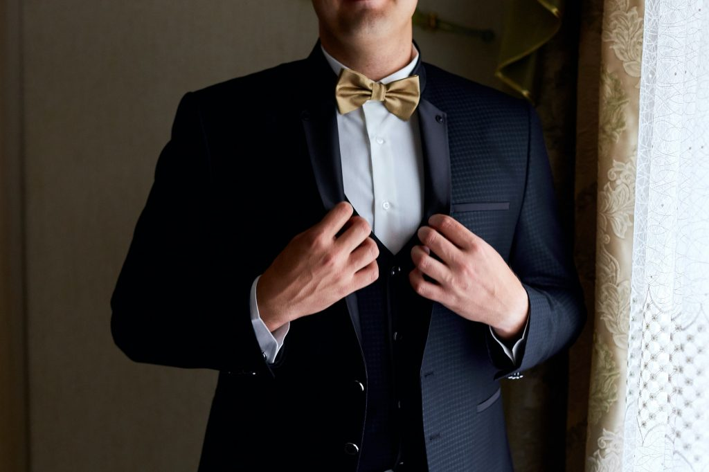 Handsome elegant young fashion man in coat tuxedo classical costume suit