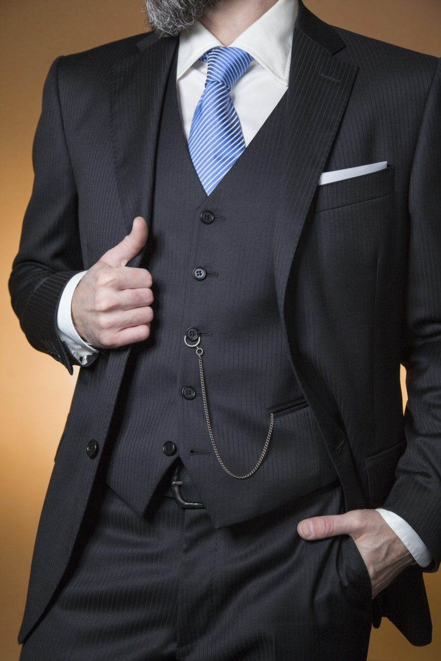 man posing with elegant pinstripe suit and all the accessories