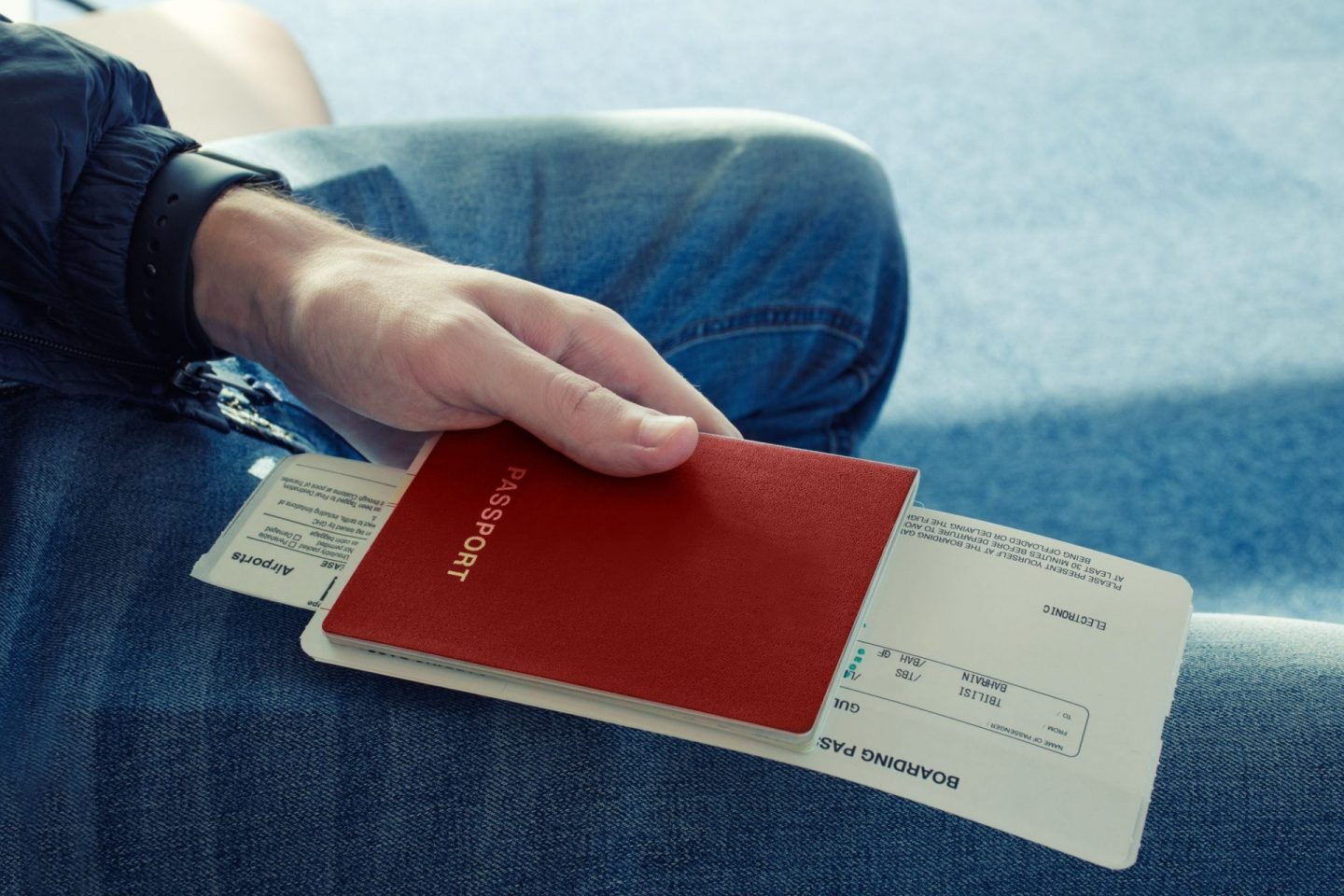 Man in blue jeans sits and holds in his hand passport of red color with tickets to plane