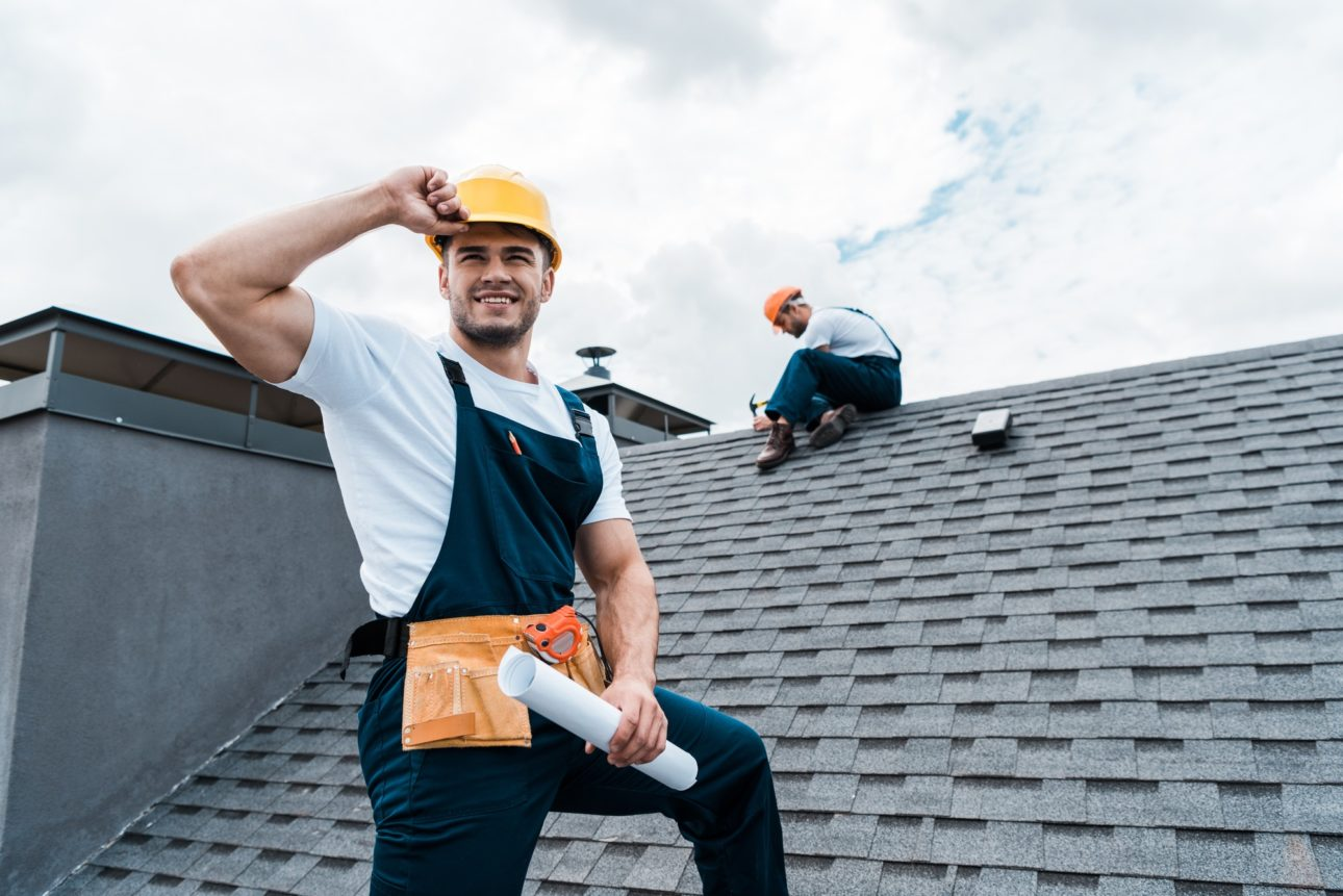 selective focus of happy repairman holding rolled paper while coworker repairing roof